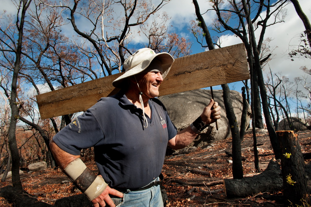 78 yr old Carl Neilsen has worked tirelessly  for 42 years at the Black Hill Reserve.He is seen here carting heavy steps up the steep slope to replace those burnt in the fires.