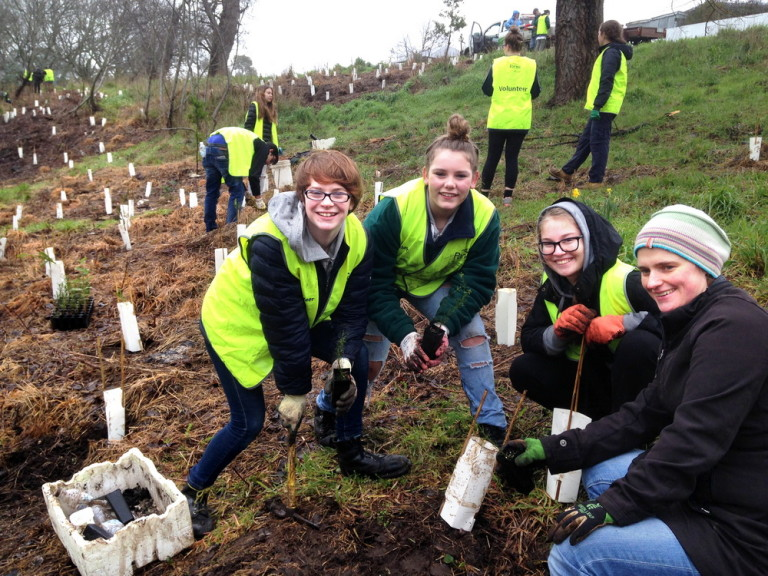 "Students from Kyneton Secondary College Estelle, Tiarna and Charlotte, with teacher Dr Anwyn Chapman, planting on National School Trees Day with the Kyneton River and Land Management Group.The group planted over 500 trees on the day. Student Georgia Brown said ""We planted a range of indigenous plants including the local threatened species,The Hairy Anchor Plant,which only grows in this part of the catchment."""
